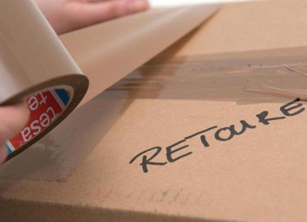 Paket mit Retoure beschriftet wird verpackt
