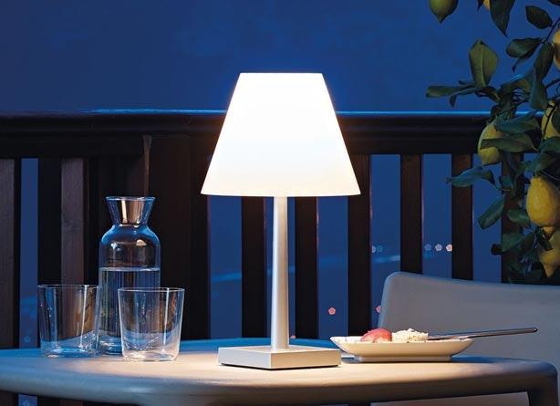 tisch im freien bei nacht mit stehleuchte neben gläsern